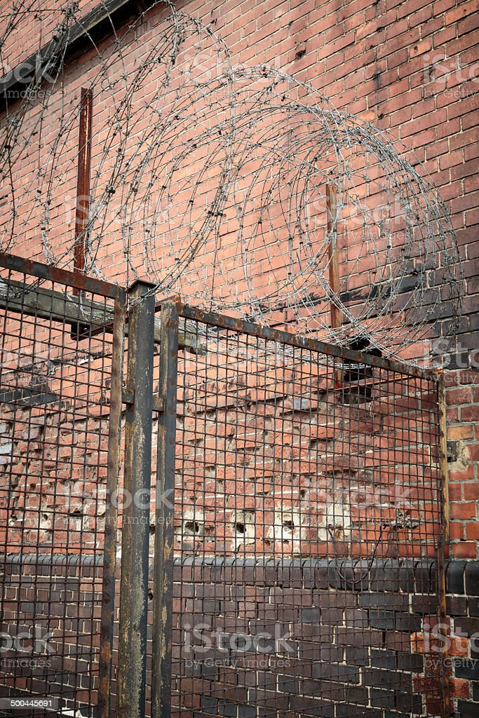 barb wire on an old fence with red brick wall stock photo