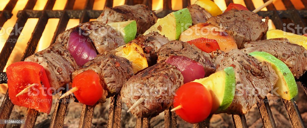 Barbecue Beef Kebabs On The Hot Grill Close-up. stock photo