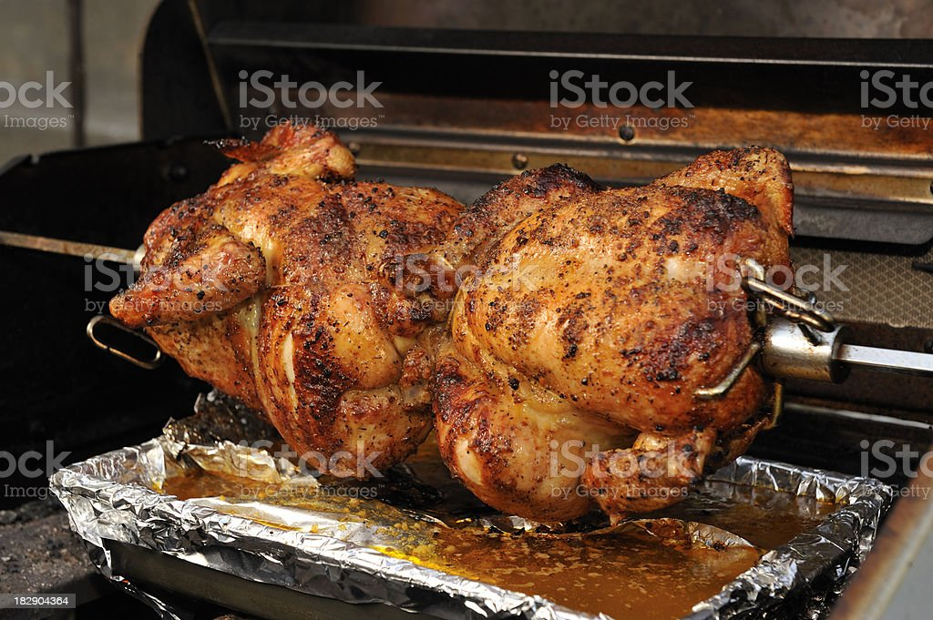 Barbecue chicken, roasting jack, spit roasted, outdoor home cooking. royalty-free stock photo