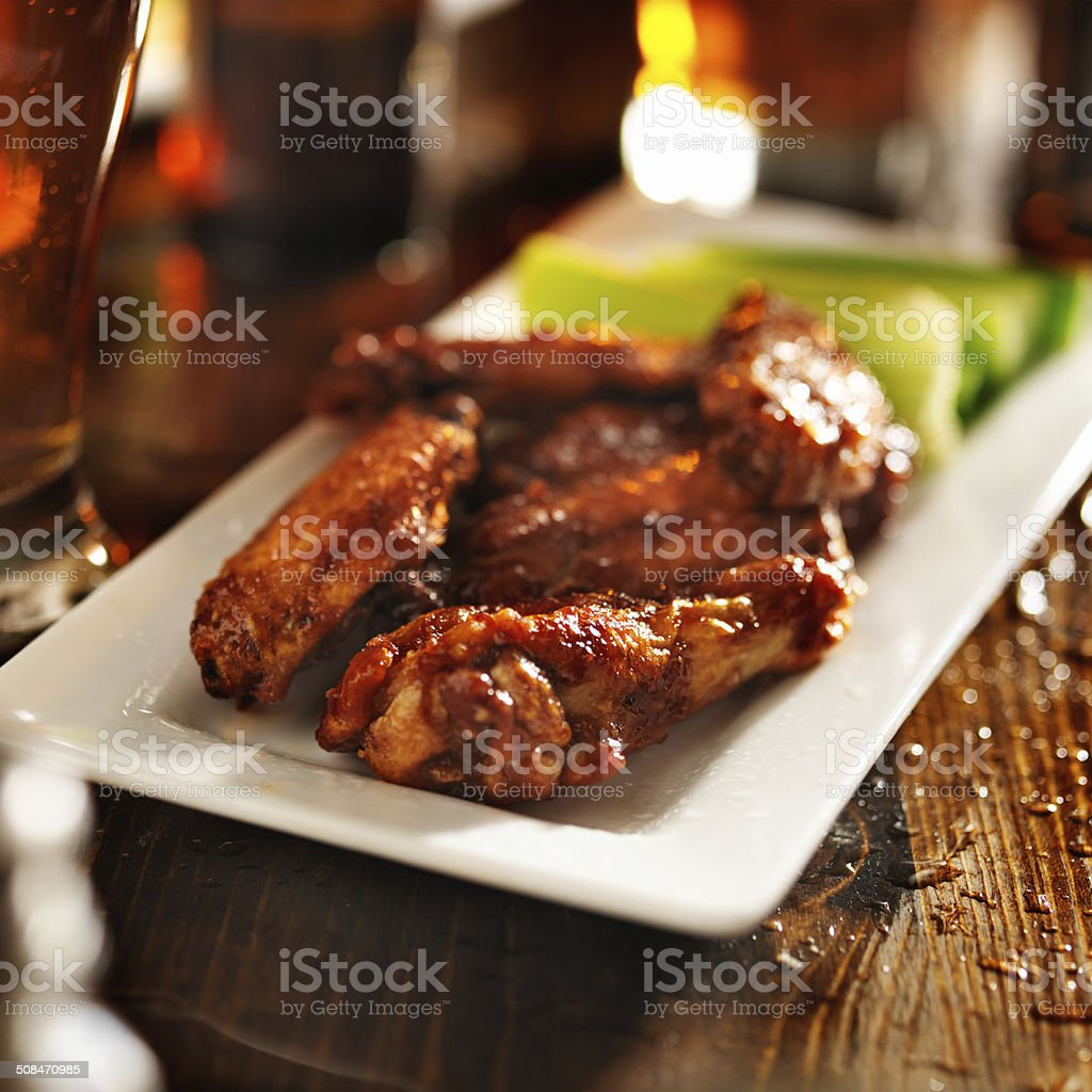 barbecue chicken wings with beer and celery stock photo