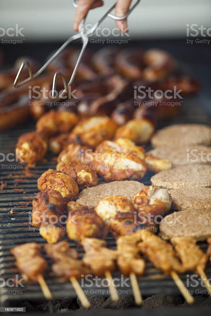 Barbecue close-up with moving chef's hand and metal tool royalty-free stock photo