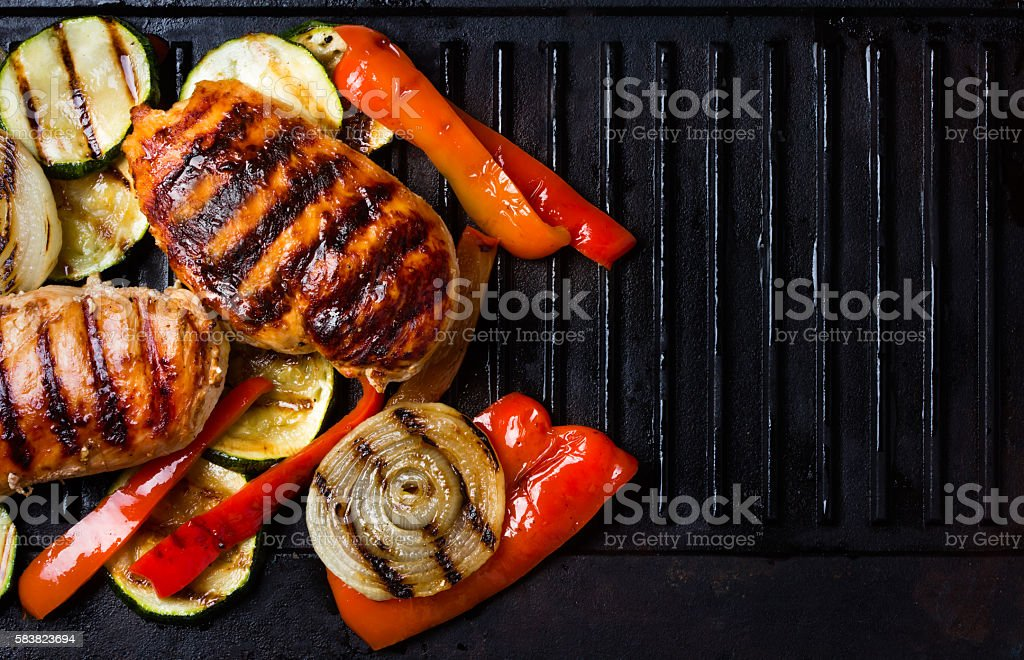 Barbecue grilled chicken and vegetables on cast iron table stock photo