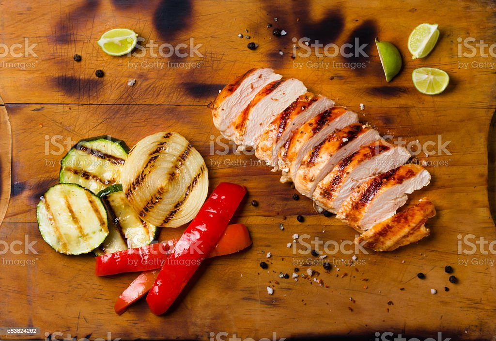 Barbecue grilled chicken and vegetables on wooden cutting board stock photo