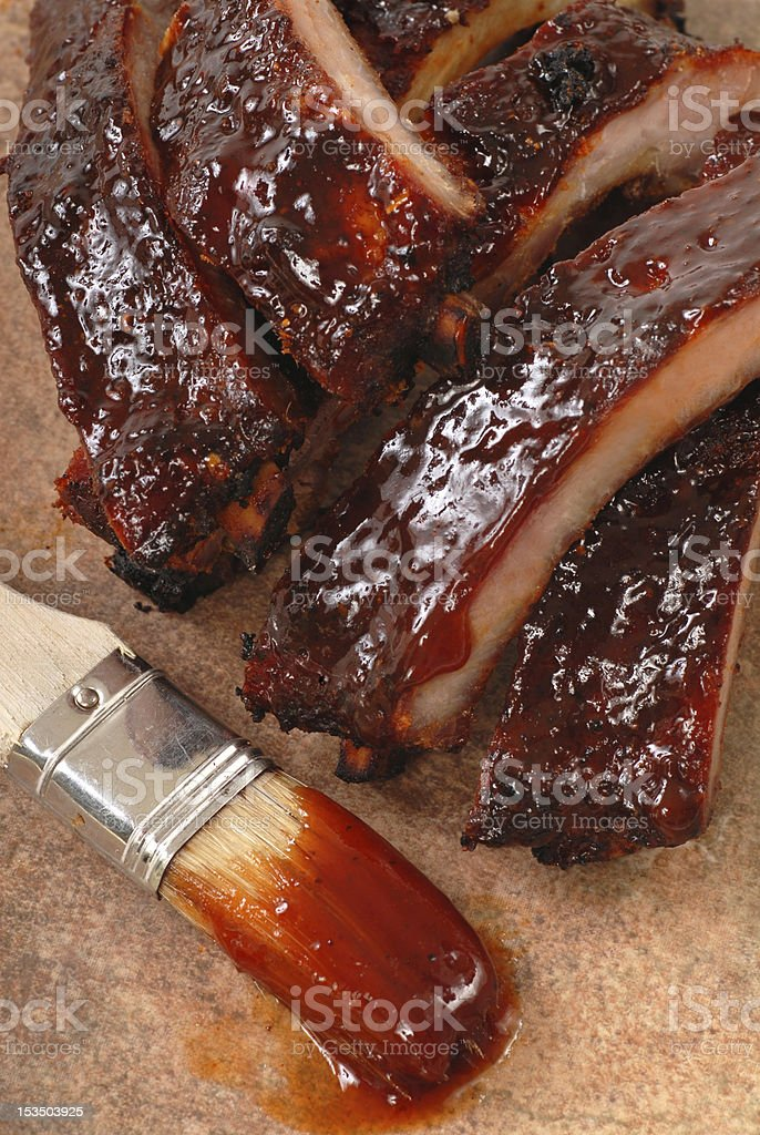 Barbecue ribs and a brush with barbecue sauce on it stock photo