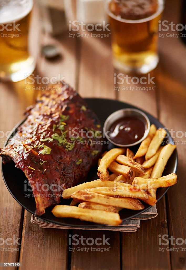 barbecue ribs with french fries and sauce on plate stock photo