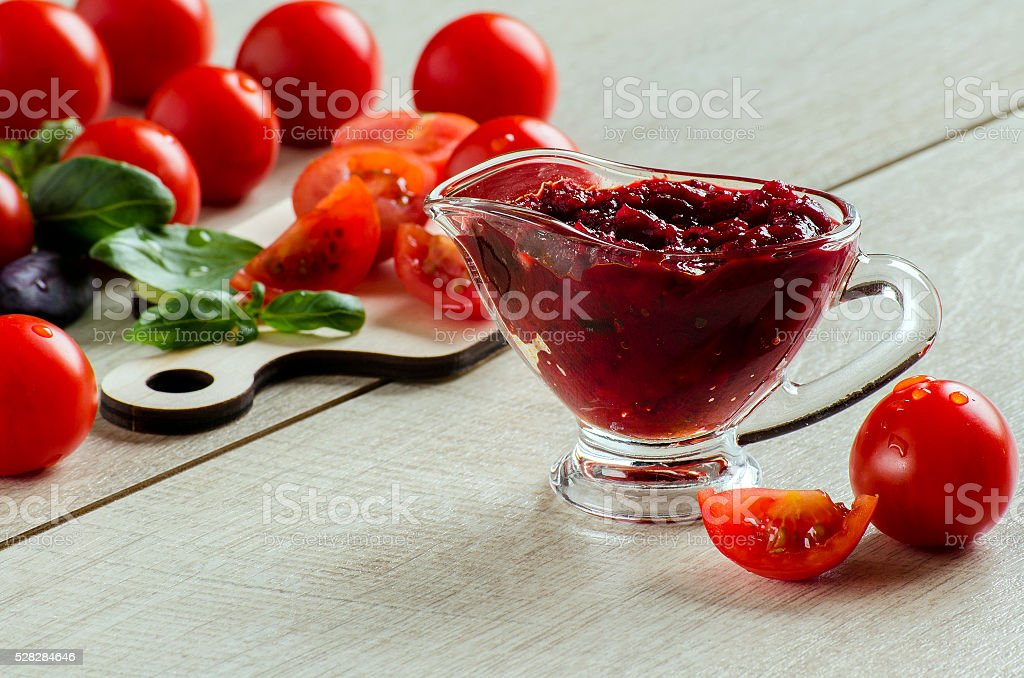 Barbecue sauce in a gravy boat, tomatoes and Basil stock photo