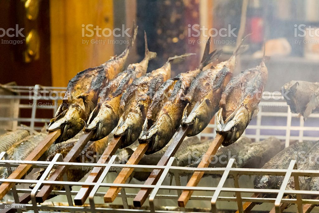 Barbecue stockfish grilled trout fish on stocks with fire smoke stock photo