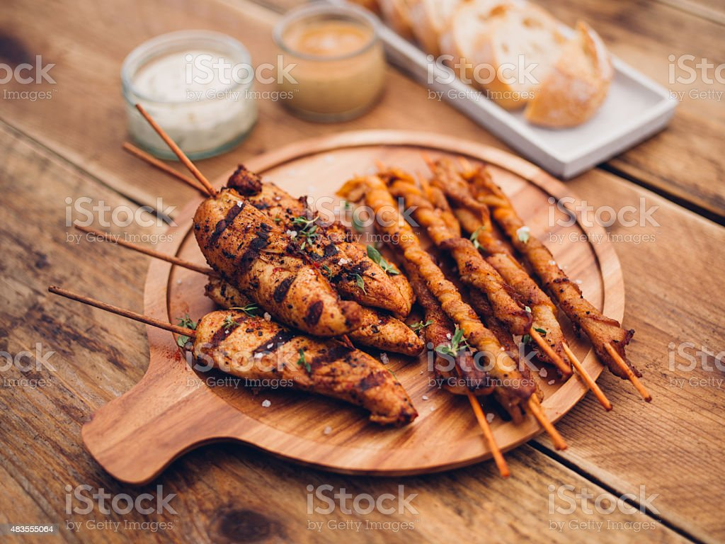 Barbecued chicken skewers and bacon twists on wooden table outdoors stock photo