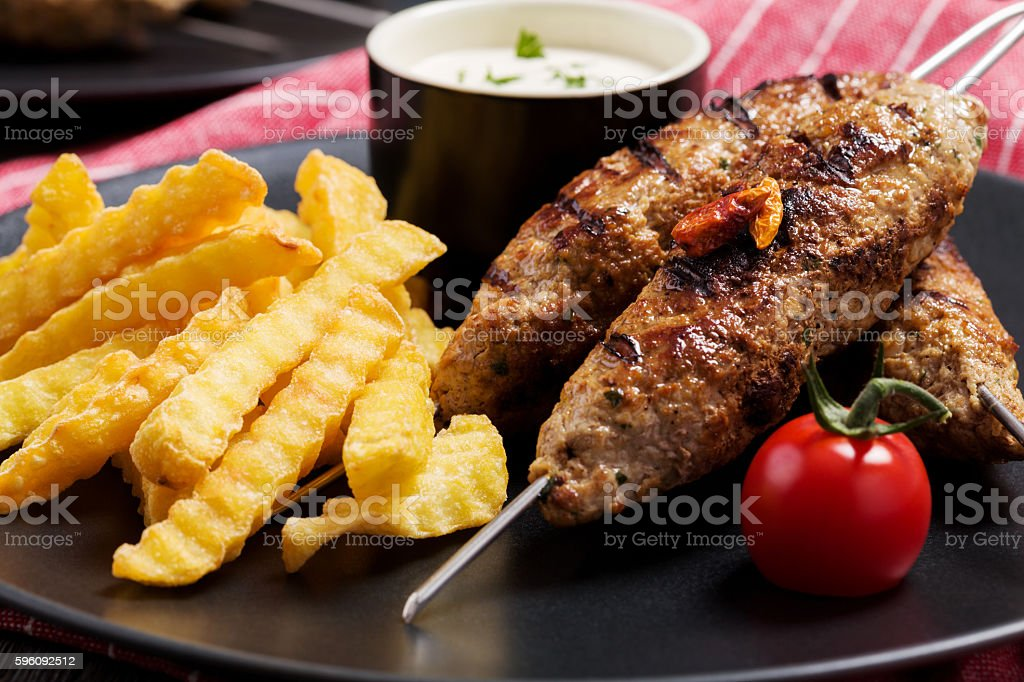 Barbecued kofta - kebeb with fries and vegetables stock photo