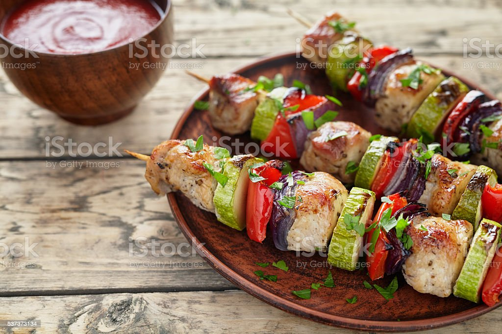 Barbecued marinated turkey or chicken meat shish kebab skewers stock photo