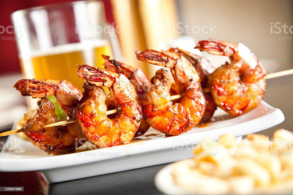 Barbecued shrimp skewers served with beer stock photo