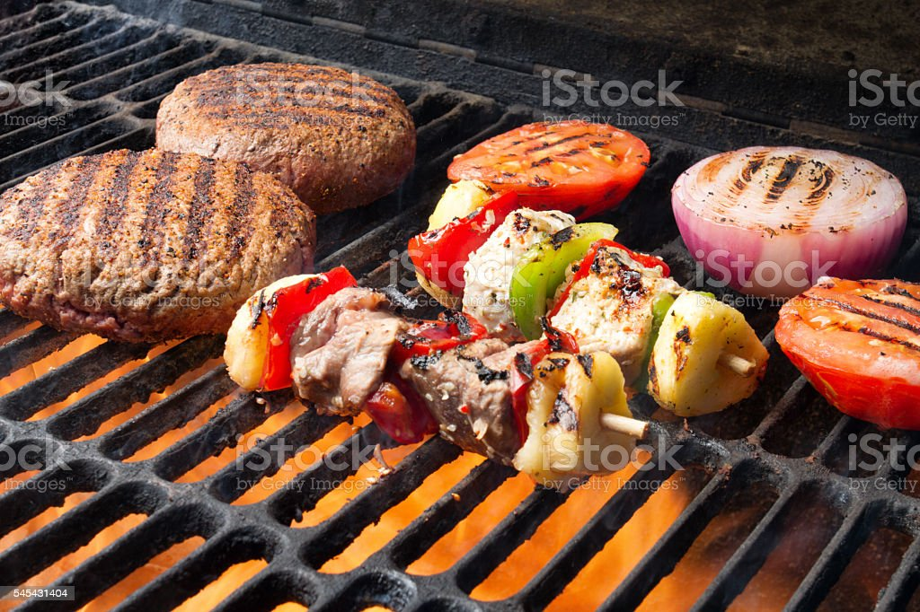 Barbecuing Burgers, Veggies And Kabobs On A Grill stock photo