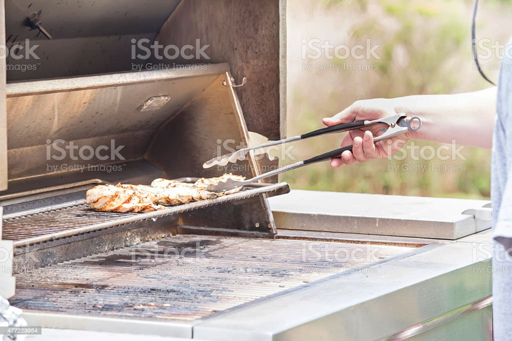 Barbecuing chicken on a outdoor gas grill stock photo