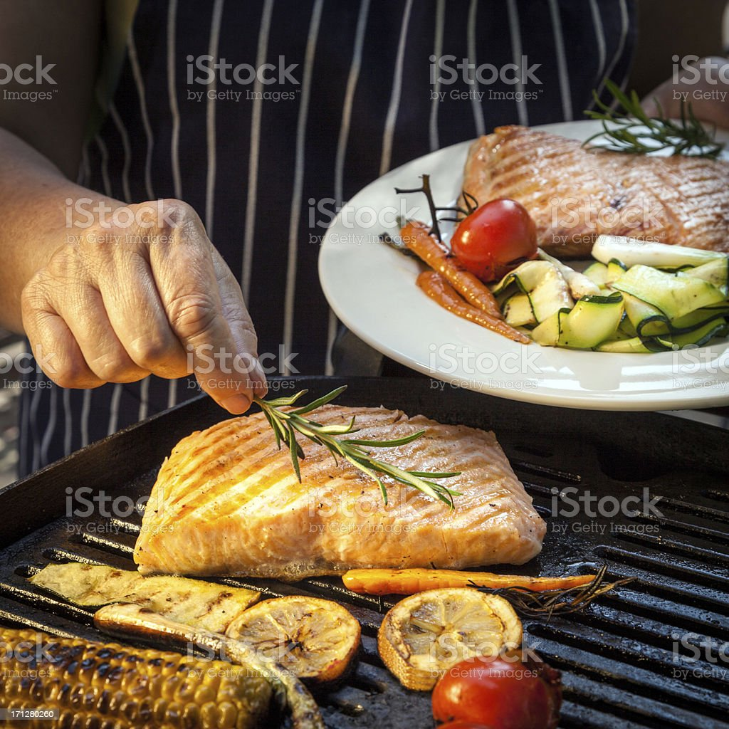 Barbecuing salmon and vegetables royalty-free stock photo