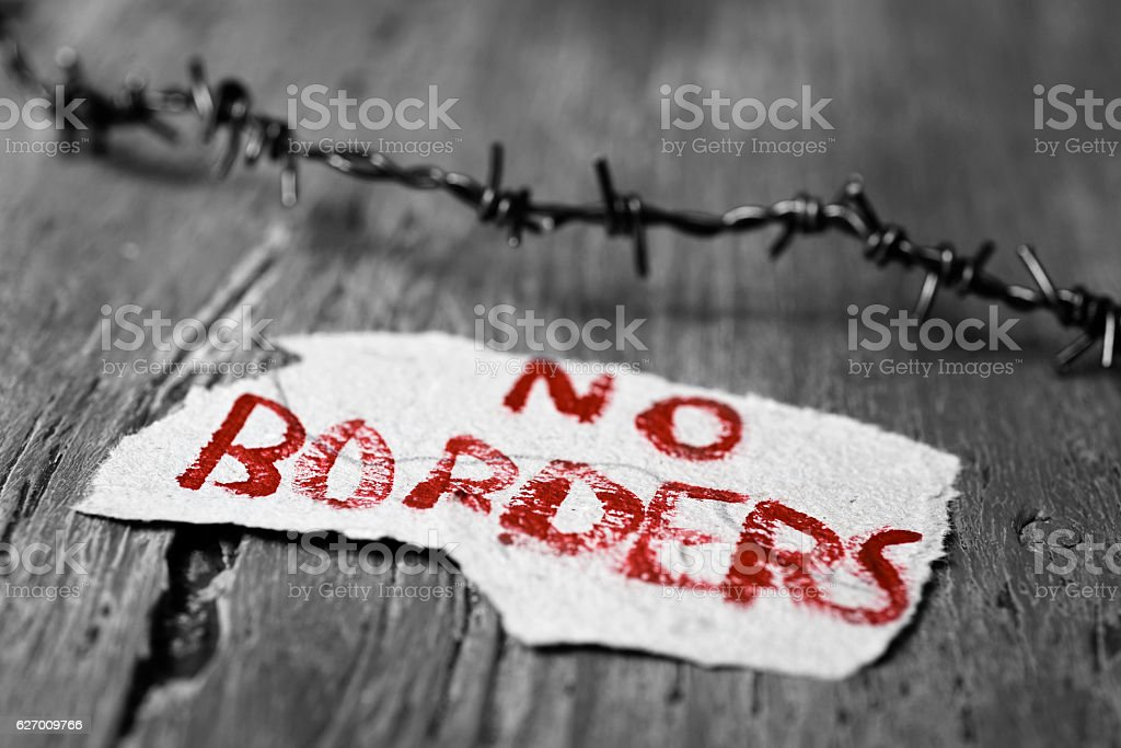 closeup of a barbed wire and a piece of paper with the text no...