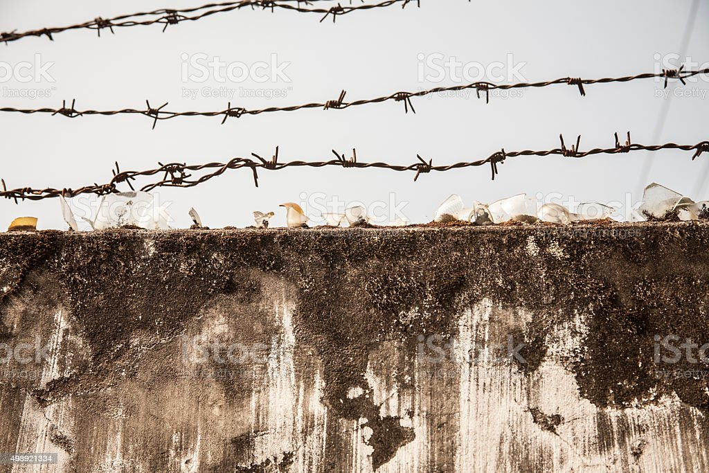 Barbed wire at top of concrete fence. National border. stock photo