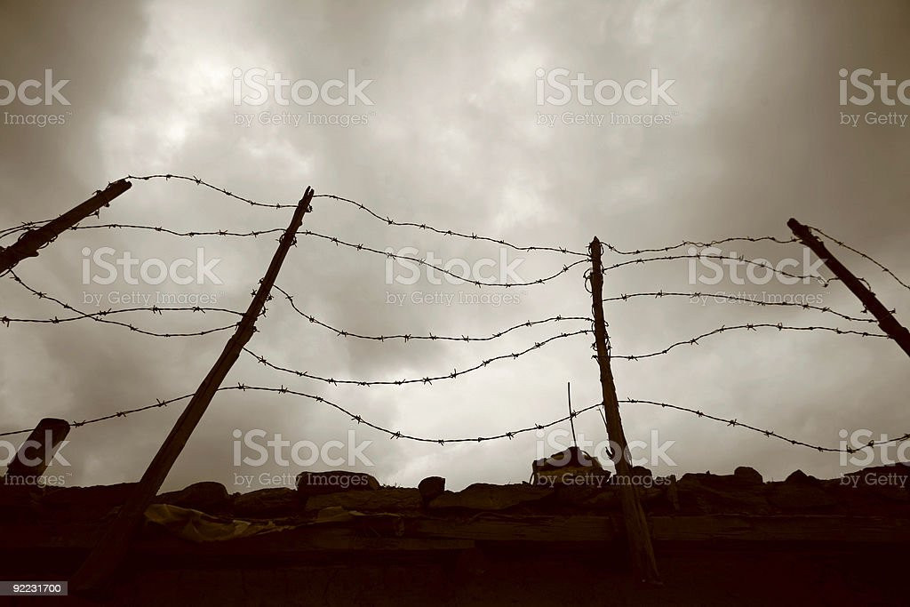 Barbed wire fence against grey sky royalty-free stock photo