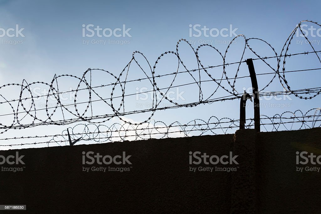 Barbed wire fence around prison walls blue sky in background stock photo