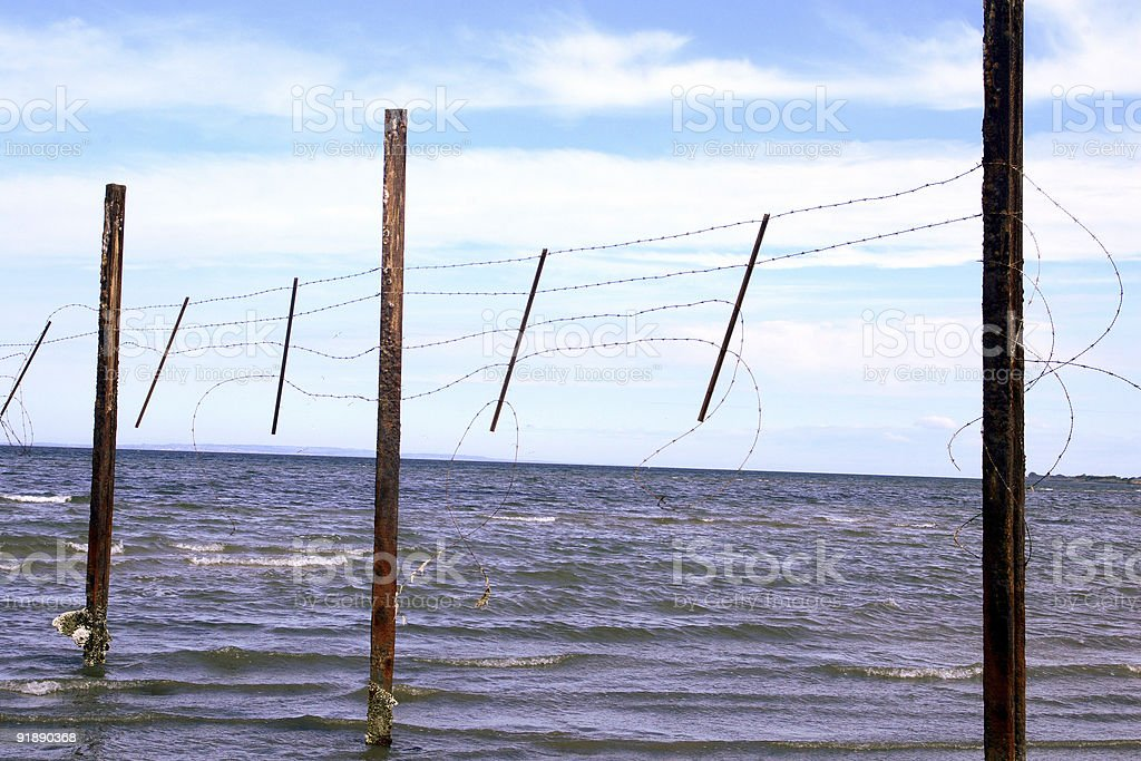 Barbed Wire Fence At Sea stock photo