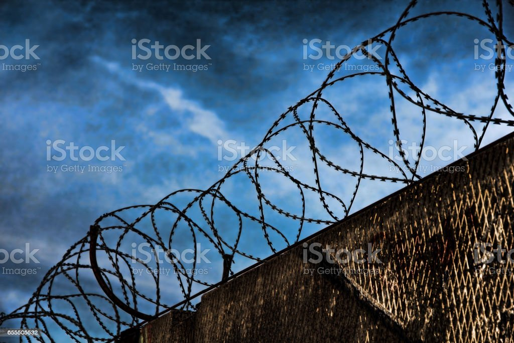 Barbed wire fence detail against of the night dramatic sky. stock photo