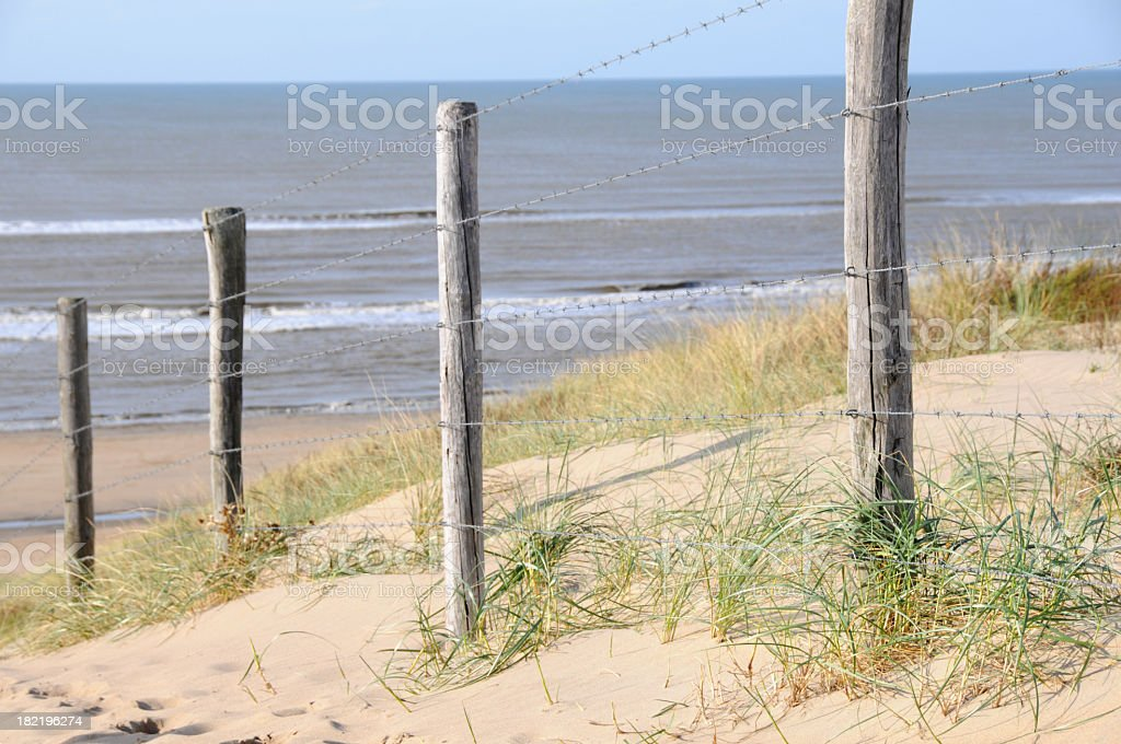 Barbed wire fence , dunes and sea royalty-free stock photo