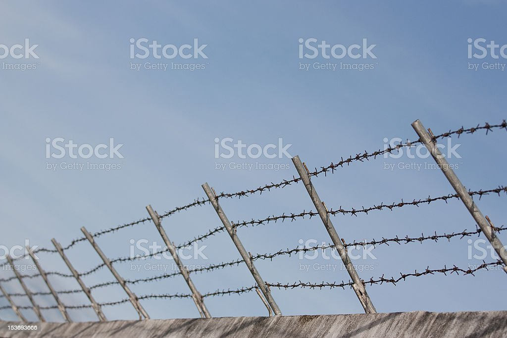 Barbed wire fence on concrete wall with blue sky background royalty-free stock photo