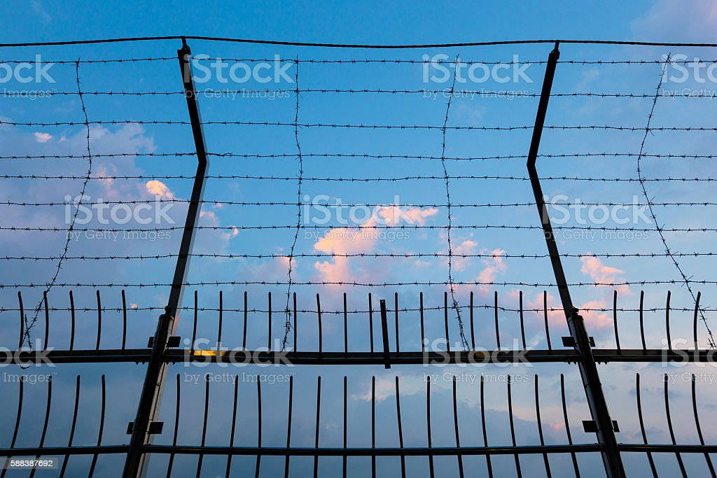 Barbed wire fence silhouettes against cloudy dark blue sky stock photo