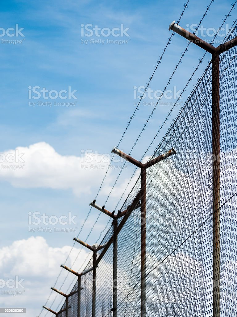 Barbed wire fence under the sky background stock photo