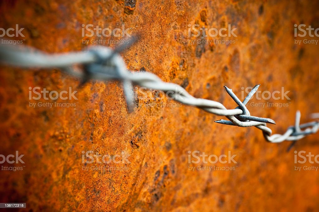 barbed wire in front of illuminated rusty metal surface royalty-free stock photo