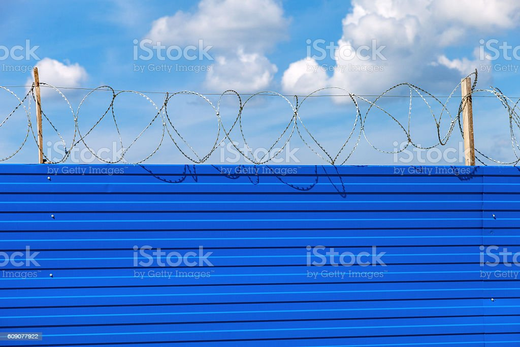 Barbed wire on the fence against a blue sky background stock photo