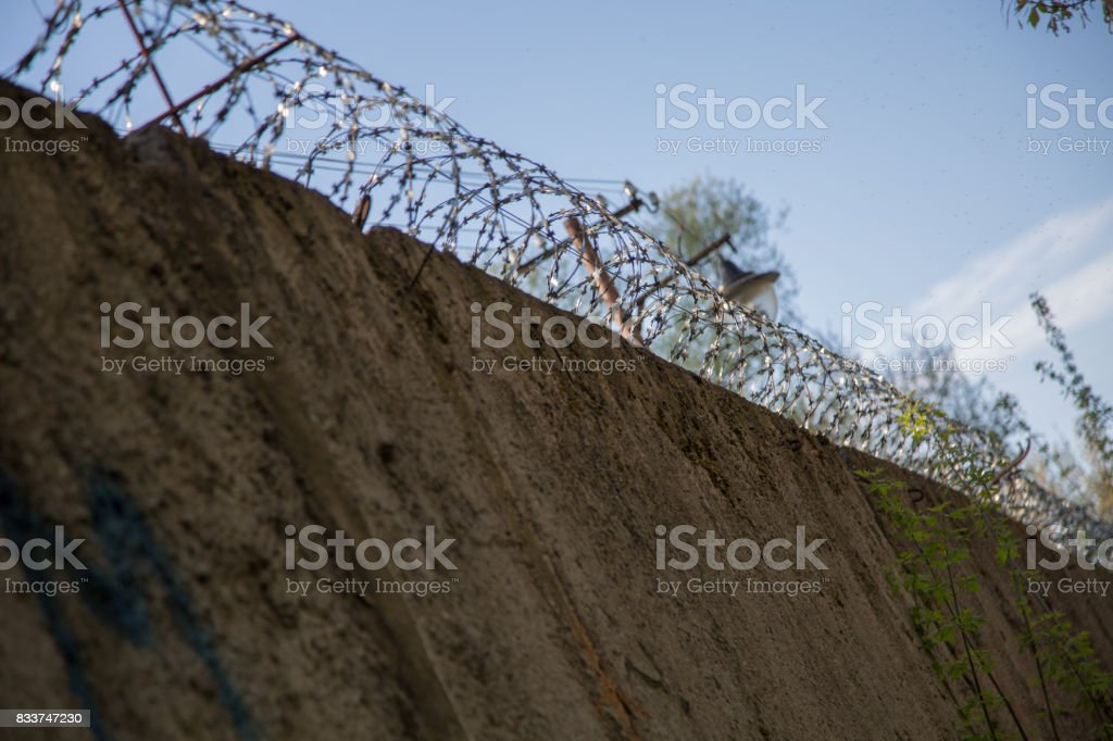 Barbed wire prison wall forbidden zone background stock photo