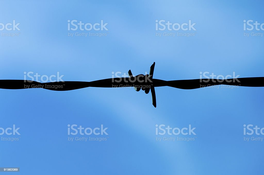 Barbed wire sillhouetted against blue sky stock photo