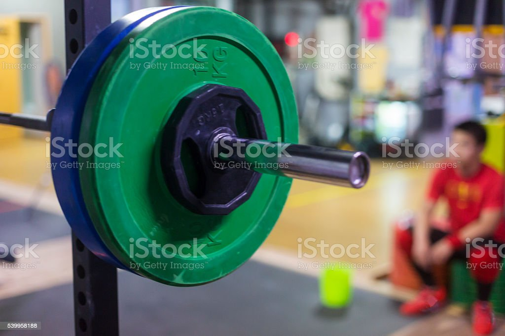 Barbell in a Cross Training Gym With a Resting Weightlifter stock photo