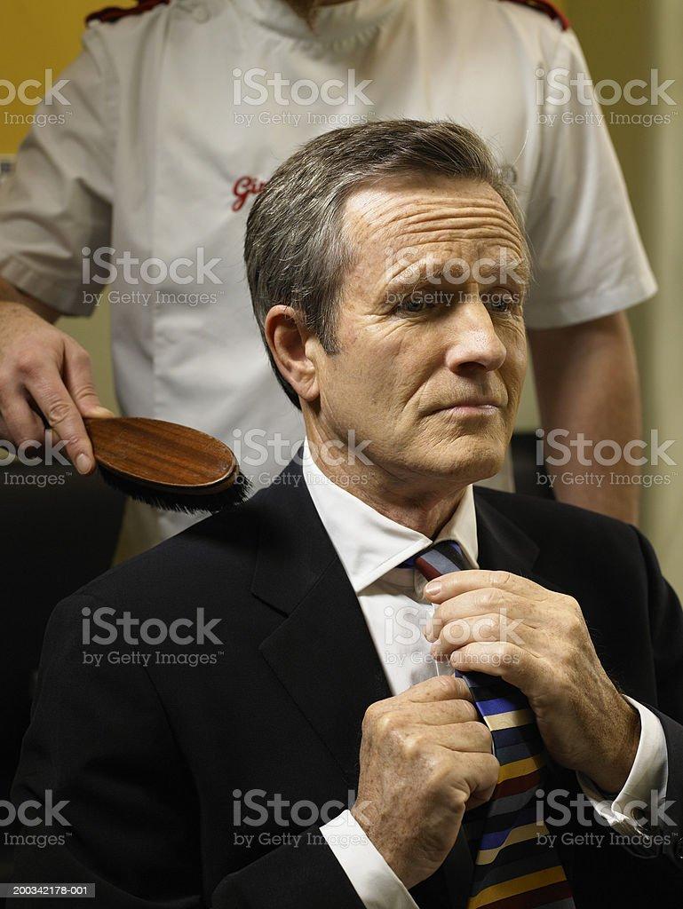 Barber brushing senior man's shoulders, man adjusting tie stock photo