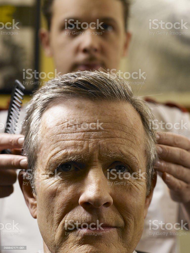 Barber cutting senior man's hair, focus on man stock photo