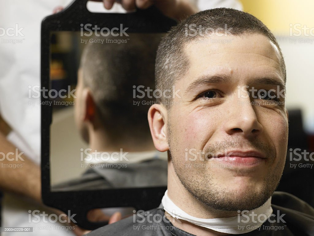 Barber holding mirror behind man's head, close-up of man smiling royalty-free stock photo