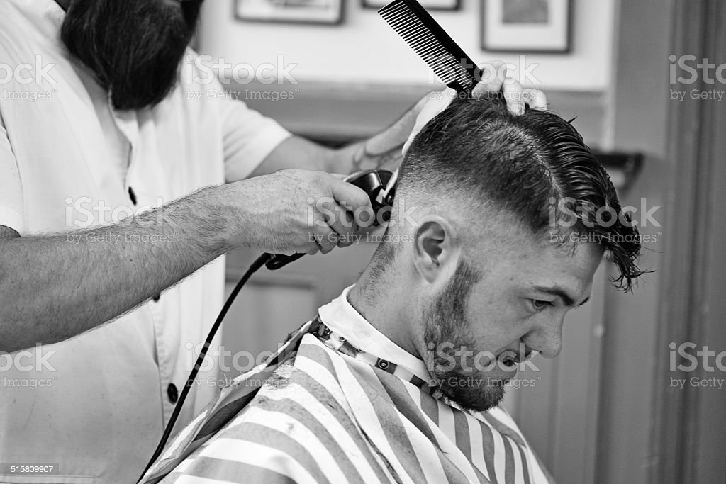 Barber shaving back of customers head stock photo