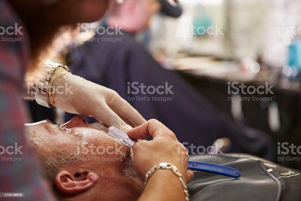 Barber Shaving Client With Cut Throat Razor stock photo
