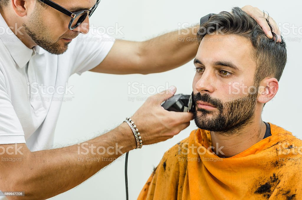 Barber takes care of customer chin with hair trimmer stock photo