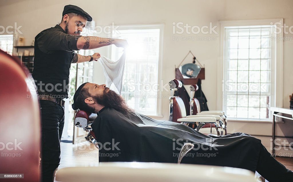 Barber taking care of client in barbershop stock photo