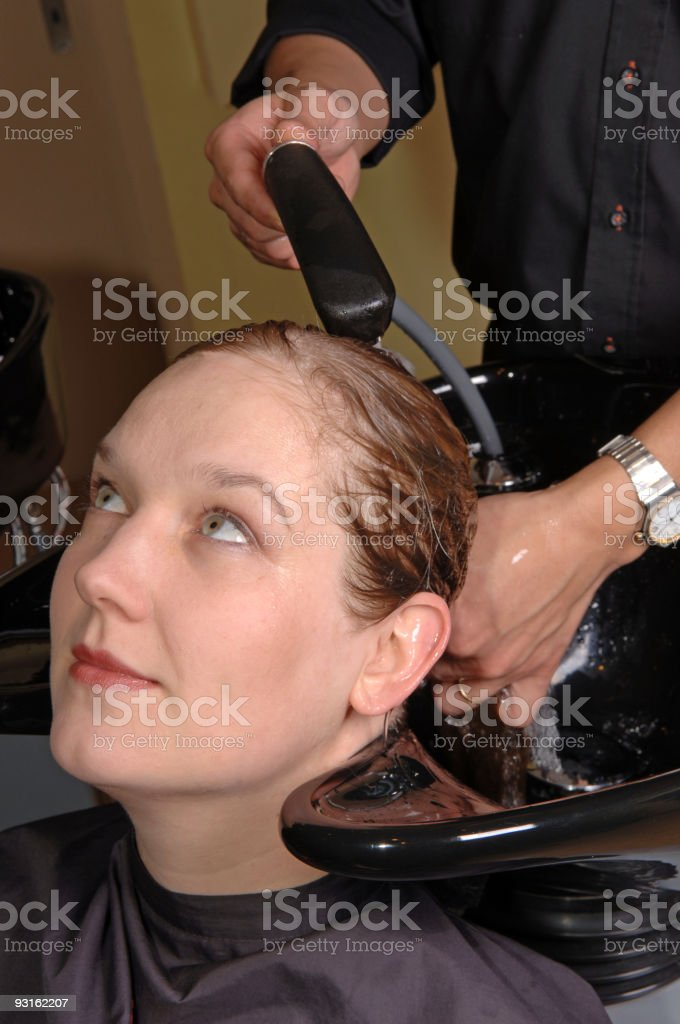 barber washing the hair of a woman royalty-free stock photo