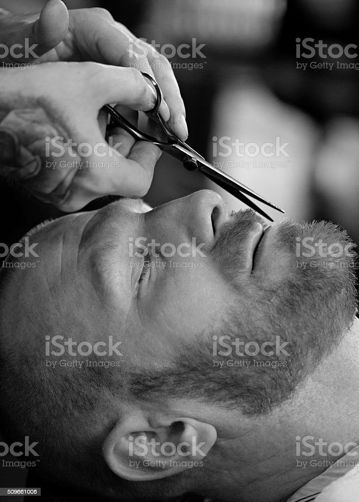 Barber with a bearded bald male client stock photo
