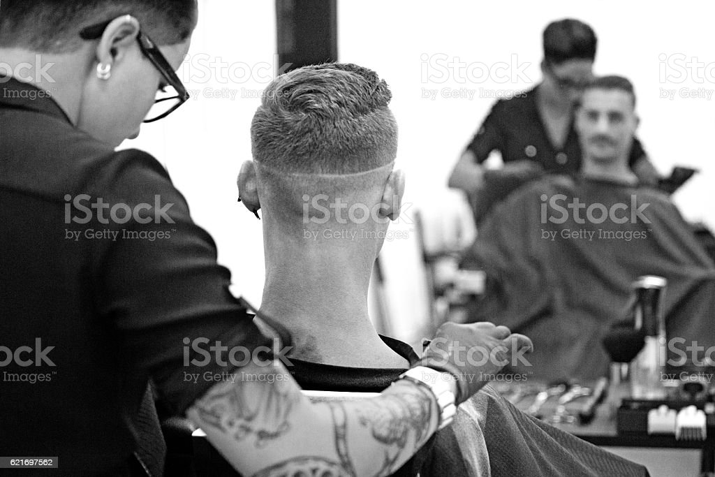 Barber working on a clients hair with mirror stock photo