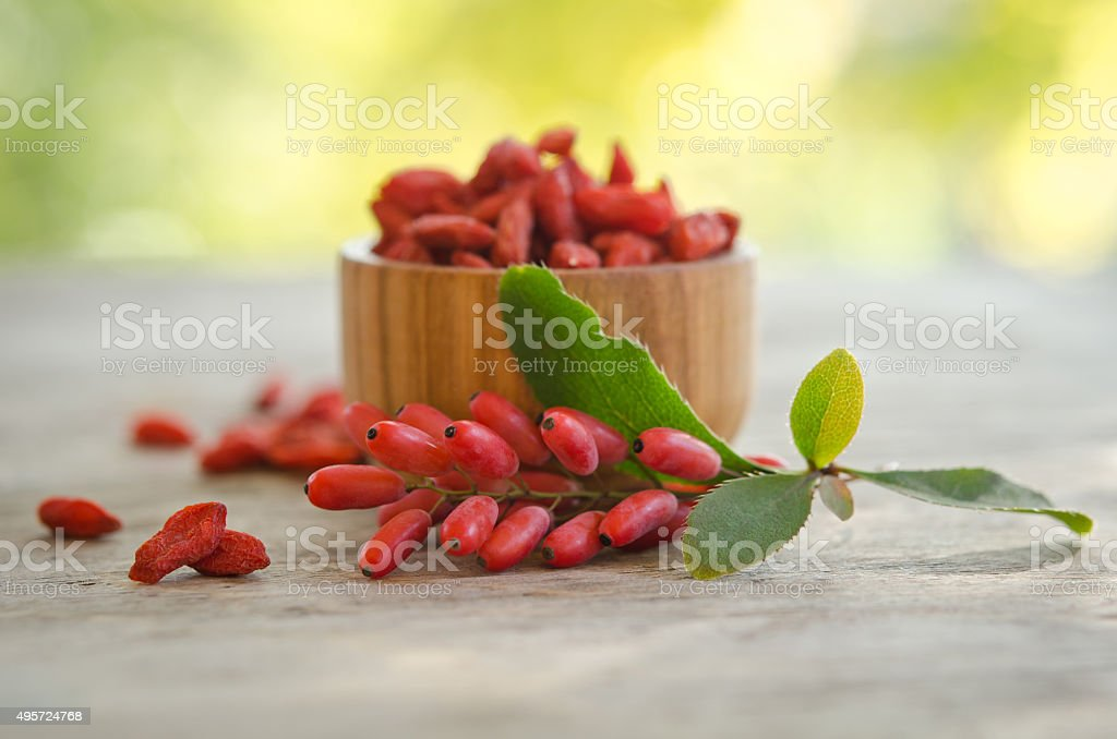 barberries and goji berries isolated on wooden table. stock photo