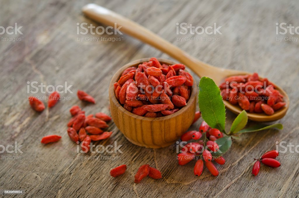 barberries and goji berries on wooden background stock photo
