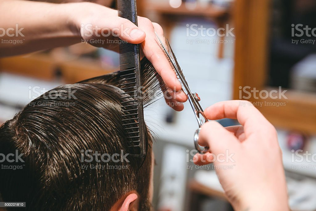 Barbers hands making haircut to man using comb and scissors stock photo