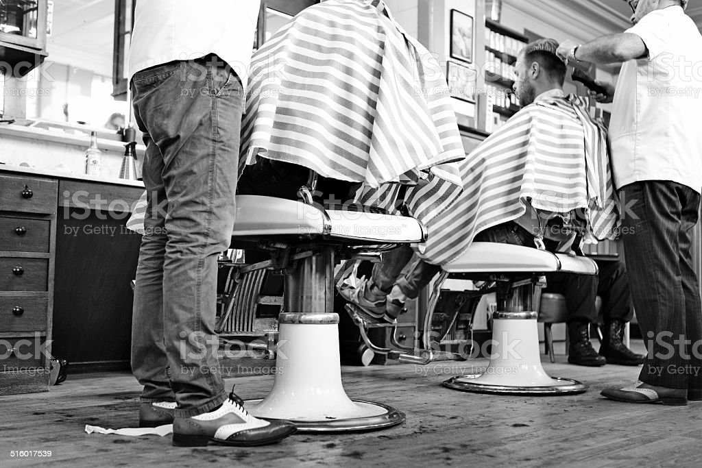 barbers working on clients in barbershop stock photo