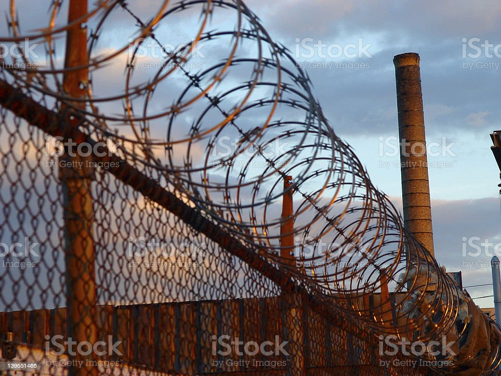 Barbwire Fence with Smokestack royalty-free stock photo