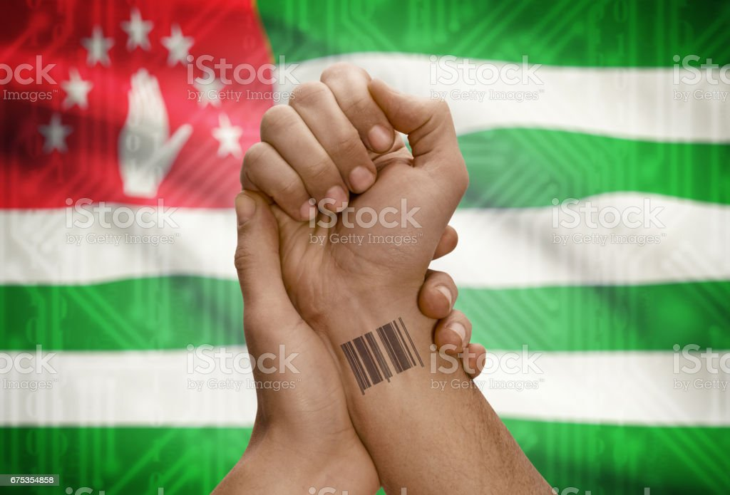 Barcode ID number on wrist of dark skinned person and national flag on background - Abkhazia stock photo