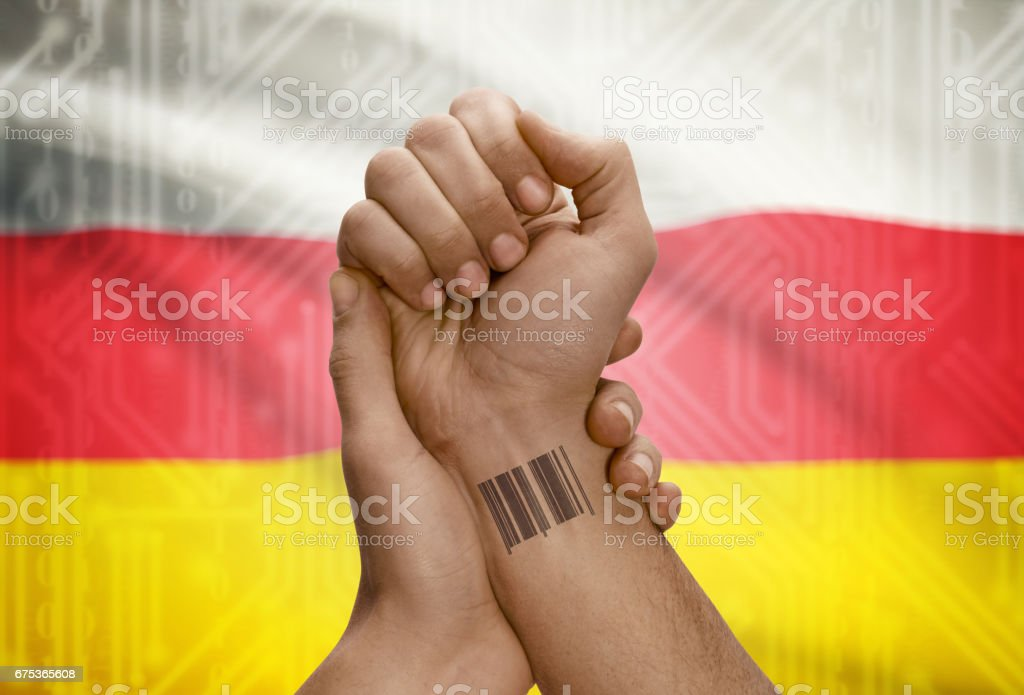 Barcode ID number on wrist of dark skinned person and national flag on background - South Ossetia stock photo